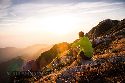 Italy, mountain running man sitting on rock looking at sunset