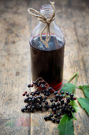 Elderberry juice and elderberries on a wooden table