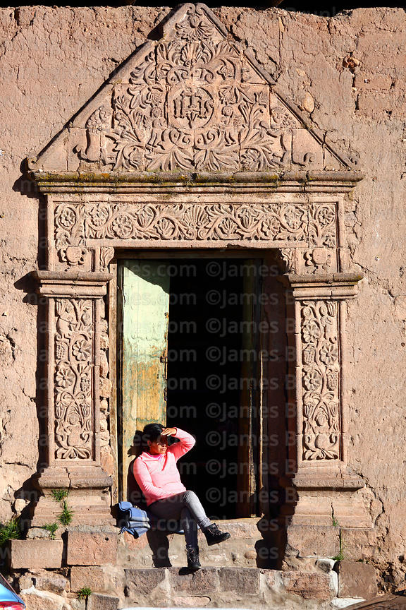 Women siiting in ornate carved stone doorway of Casa de la Inquisición, Plaza de Armas, Juli, Puno Region, Peru