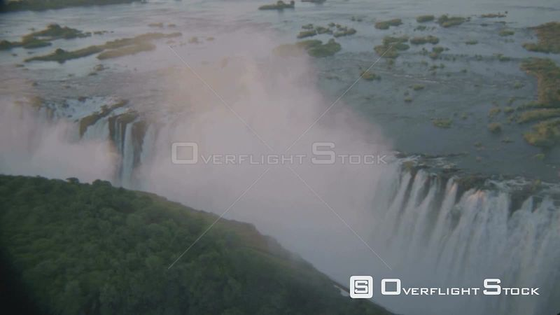 Aerial wide angle shot along lip of waterfall with sun reflecting on river and mist at sunset sunrise, forest in foreground V...
