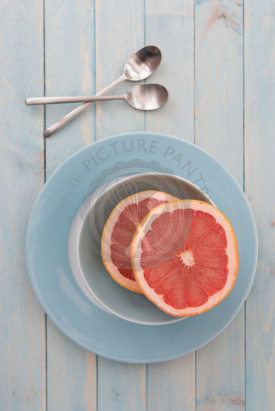 Pink grapefruit halved in a bowl.