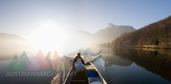 Austria, Mondsee, View of fisherman in boat near lake