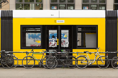 Yellow Tram Carriage with Bicycles leaning on Railings