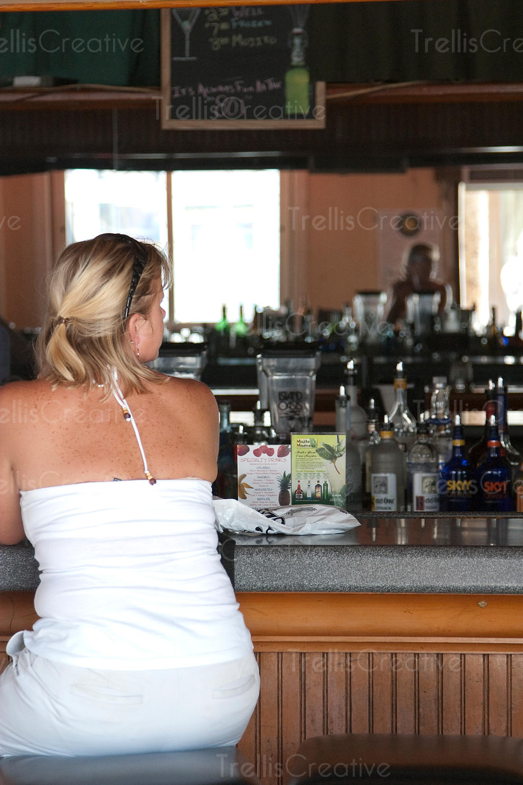 Young woman sits at on a stoll in a bar