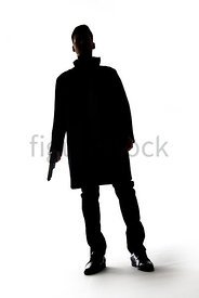 A Figurestock image of a mystery man standing, holding a gun, in silhouette – shot from low level.