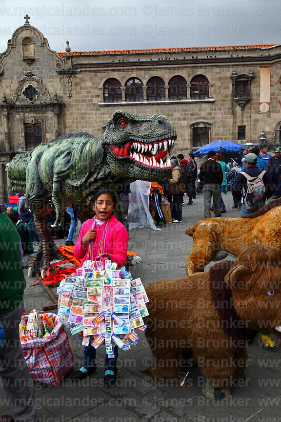 Girl selling miniature bank notes in front of model dinosaur at Alasitas festival, La Paz, Bolivia