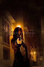An atmospheric image of a woman with a gun in an urban street in Valencia, Spain.