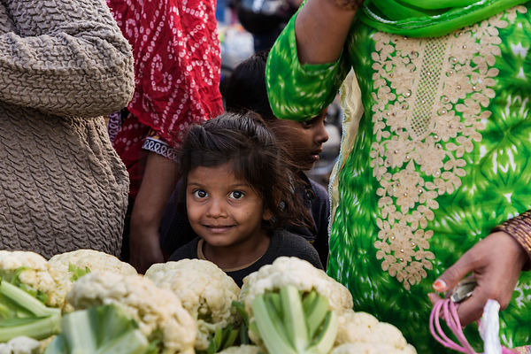 Portrait of a Young Chld with her Mother at a Vegetable Parket.