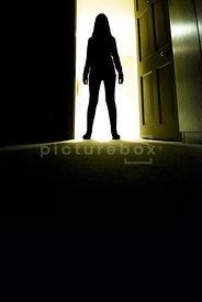 An atmospheric image of the silhouette of a girl standing in a doorway into a dark room.