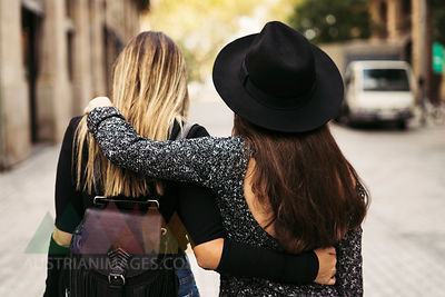 Back view of two women walking on the street