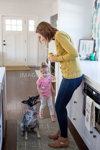 Woman and Little Girl In Kitchen with Sitting Dog