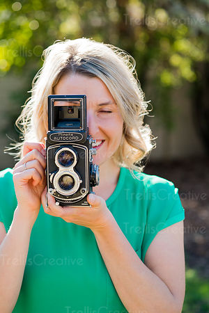 Pretty blonde woman holding an old camera in front of her face