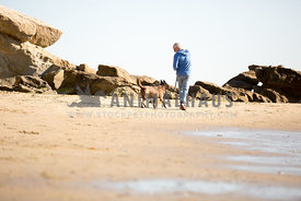 manwalking on the beach with dog