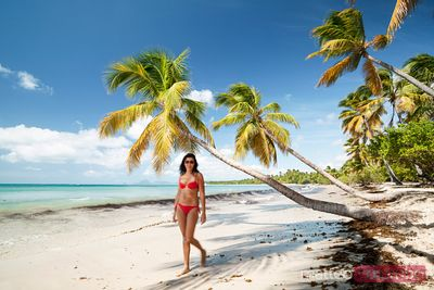 Woman in red bikini walking on tropical beach in the Caribbean