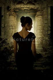 An atmospheric image of a mystery woman standing in front of the door of an old, dark, stone building.