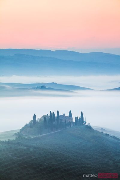 Misty sunrise over farmhouse, Tuscany, Italy