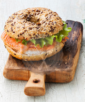Salmon Bagel Sandwich with cream cheese and grain on blue wooden background