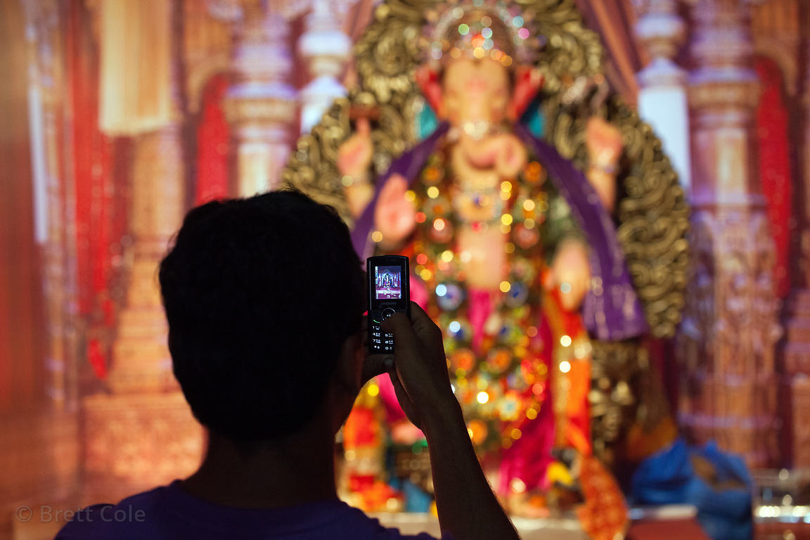 A visitor uses a mobile phone to photograph a Ganesh Idol at a pandal in Lalbaug, Mumbai, India.