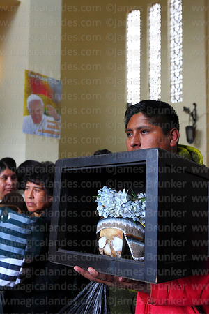 Man with his skull in front of poster of Pope Francis in church during mass, Ñatitas festival, La Paz, Bolivia