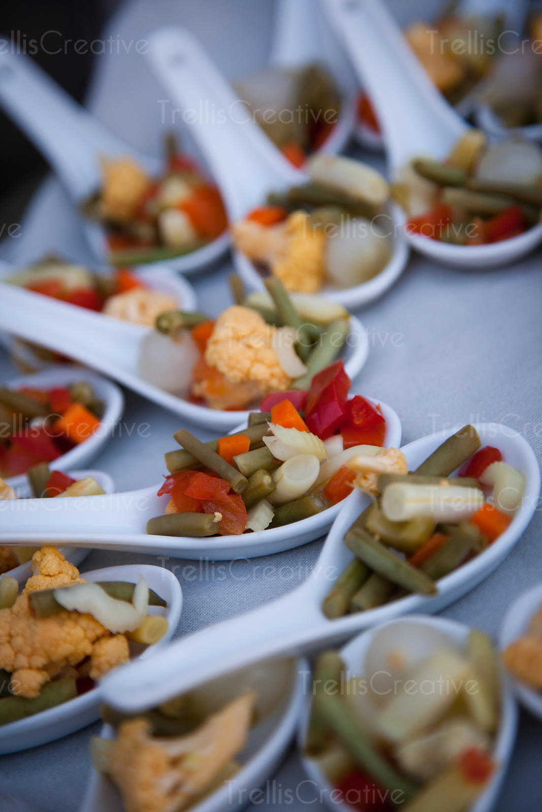 Marinated vegetables served on individual white spoons