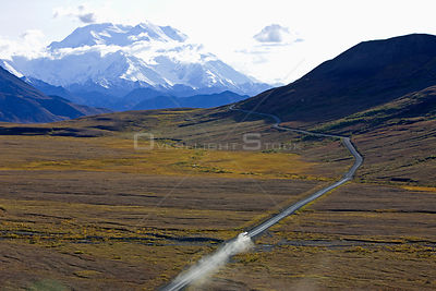 Aerial view of vehicle travelling along road across Denali National Park,  with Mount McKinley in the background, Alaska, USA...