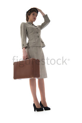 A 1940's woman in a suit and hat, standing with a suitcase – shot from low-level.