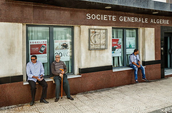Men sitting on window sills of Society Generale in Algiers, Algeria, North Africa
