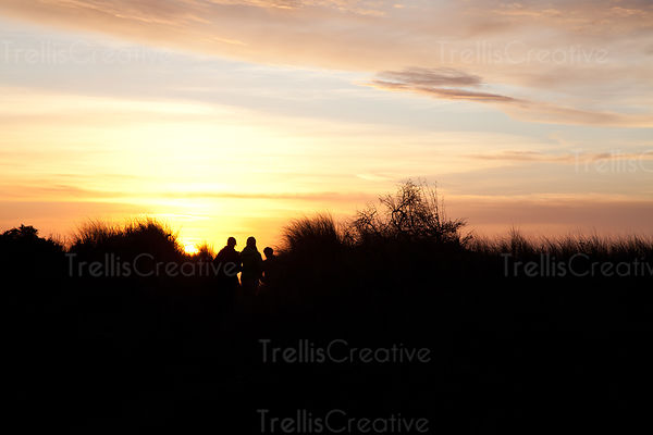 The silhouette of people hiking along a beach trail at sunset