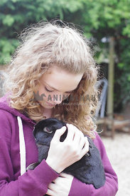 Young blonde girl holding and stroking black bunny rabbit