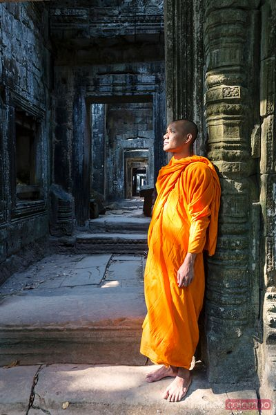 Buddhist monk standing inside Angkor Wat temple, Cambodia