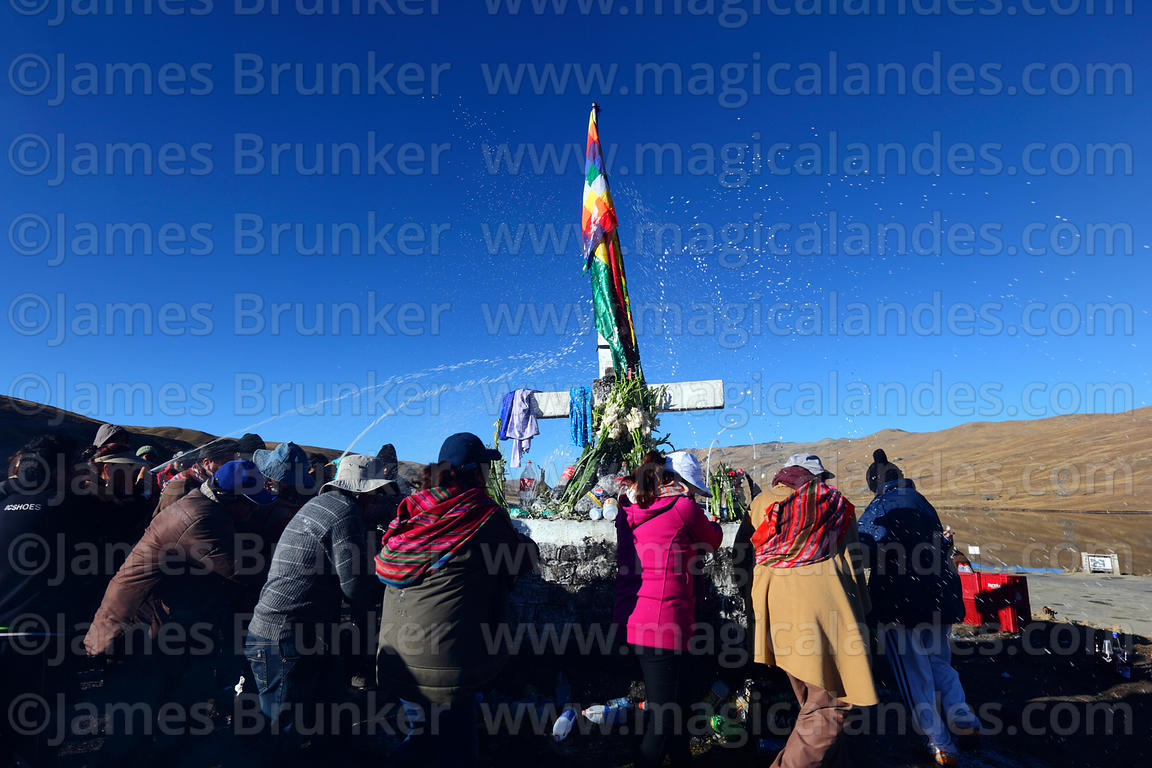 People spraying beer over cross and altar while making offerings to Pachamama, La Cumbre, Cordillera Real, Bolivia