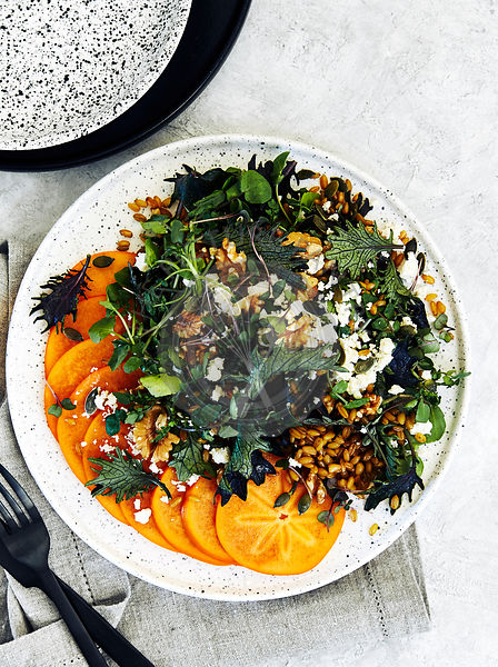 Healthy persimmon and farro salad with kale, watercress, goat cheese and nuts.