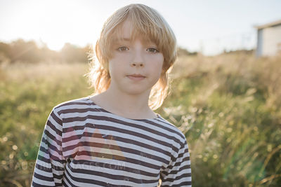 Portrait of blond boy at backlight