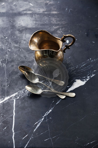 Vintage Kitchenware Silver milk jug and teaspoons on black marble background