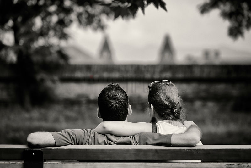 Couple Sitting on a Bench in the Evening