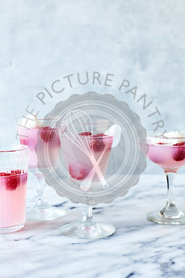 Pink lemonade jelly with raspberries on light marble background