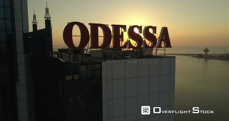 Drone tracks past the massive sign for Odessa on the Odessa Hotel with the sun rising behind. Ukraine