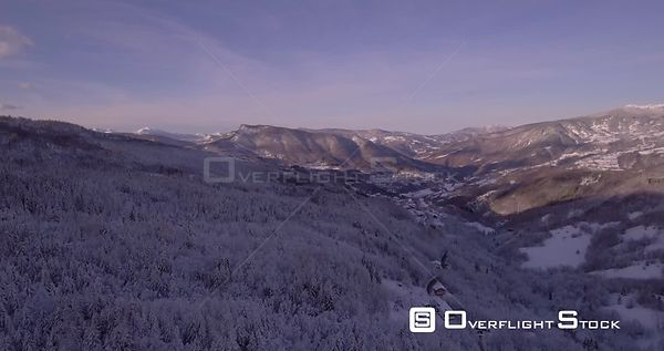 Aerial, beautiful woods under the snow and the view on the snowy mountains with ski tracks