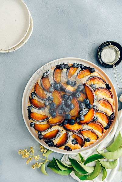 Peach cake with blueberries dusted with powdered sugar