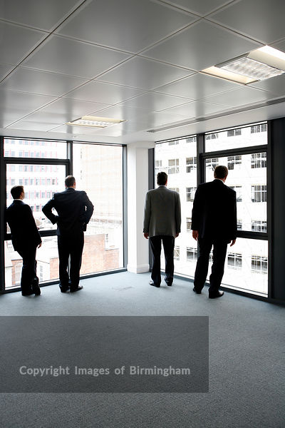 Business men looking out of the windows at the view in a new office development.