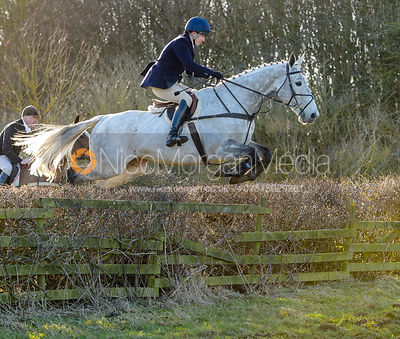 Harriet Walker jumping a hedge at Town Park Farm - The Cottesmore at Town Park Farm