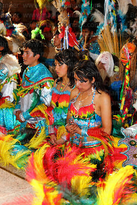 Tobas dance group kneeling during mass inside Sanctuary of Virgen del Socavón, Oruro Carnival, Bolivia