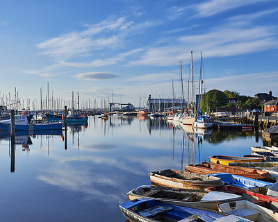 Early morning at Lymington Town Quay.  First sun & clouds over a mirror calm Lymington River. A view including colourful tenders, yachts, motor boats and Berthon Marina.