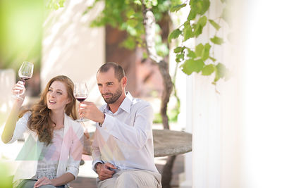 Couple sitting outdoors tasting red wine