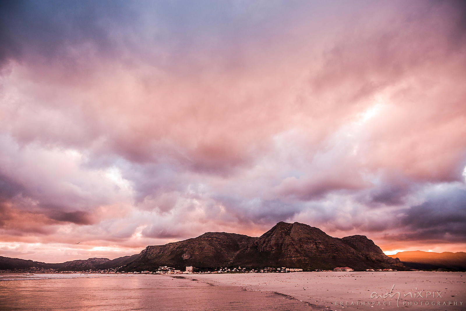Clouds glow pink and purple over the mountain at sunset.