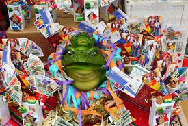 Chinese Jin Chan money toad and miniature banknotes, flight tickets and passports for sale on stall, Alasitas festival, La Pa...