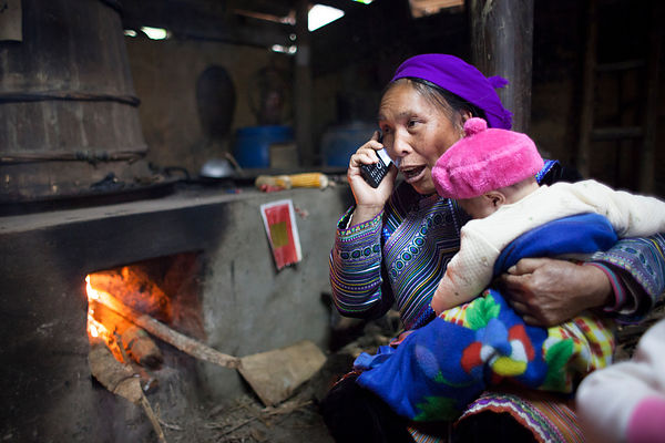 Femme passant un appel téléphonique devant son feu, Bac Ha, Vietnam / Woman passing a phone call in front of her fire, Bac Ha...