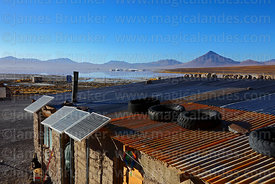 Solar panels next to adobe house, Laguna Colorada in background, Eduardo Avaroa Andean Fauna National Reserve, Bolivia