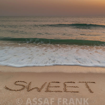 Sand writing - Word Sweet written on beach