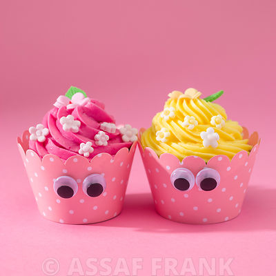 Decorated cupcakes on pink background